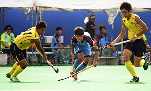 ホッケー男子 懸命にボールを追う置賜農の選手(中央) ©読売新聞社