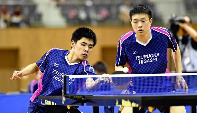 卓球男子団体決勝で力強いプレーを見せる鶴岡東の中橋敬人(左)と星翔太 ©読売新聞社