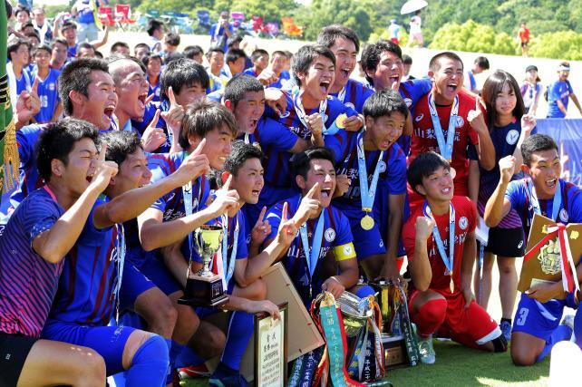 サッカー男子で優勝し、記念撮影で笑顔を見せる山梨学院の選手たち ©読売新聞社
