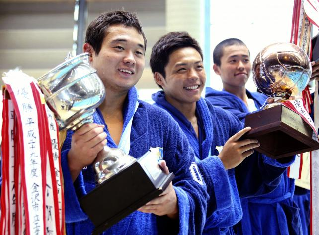 水球で3連覇を達成し、優勝杯を手に笑顔の金沢市工の(左から)宮沢拓夢、原宏斗ら ©読売新聞社