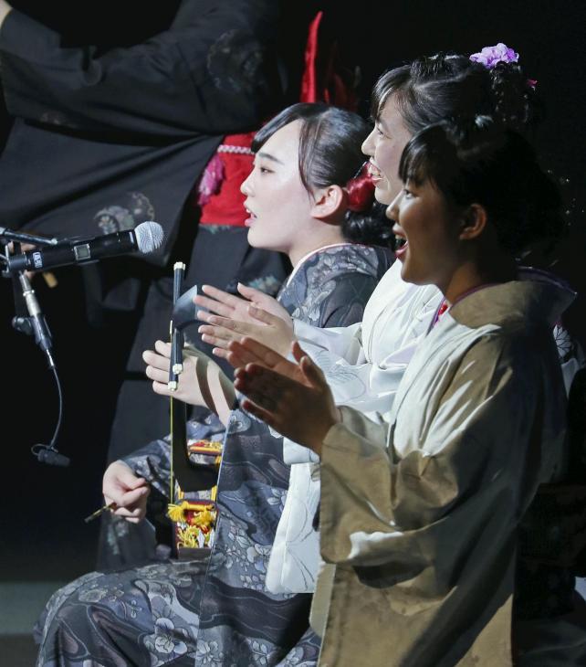 総合開会式で島唄を披露する岩崎日向子さん(左)(27日午前、鹿児島市の鹿児島アリーナで)=秋月正樹撮影