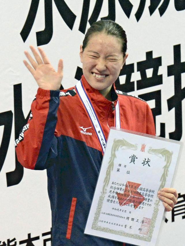競泳女子100メートル背泳ぎで優勝し、表彰台で笑顔を見せる武南の酒井夏海