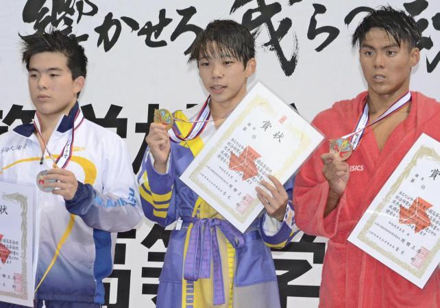 競泳男子200メートルバタフライで優勝し、表彰台で笑顔を見せる昭和学院の寺門選手(中央)と、準優勝した東海大浦安の井上選手(左)
